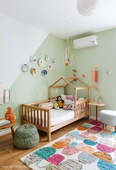 Quarto de menina com parede verde menta, quadros decorativos, tapete colorido e cama de madeira com formato de casinha.