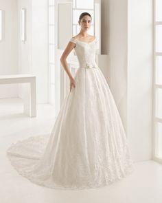 Vestido princesa de encaje y pedrería con escote barco y espalda a caja con doble lazo, en color natural.