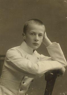 Príncipe Oleg Constantinovich em cerca de 1907. Ele está sentado para trás em uma cadeira de madeira virado para a direita. Seu braço direito está descansando na parte traseira da cadeira e sua mão esquerda está apoiando a cabeça. Ele está vestindo uma jaqueta de cor clara.