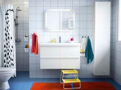 Ein Badezimmer mit weißen Fliesen, GODMORGON Waschbeckenschrank mit 2 Schubladen Hochglanz weiß und weißem ODENSVIK Waschbecken, GODMORGON Hochschrank Hochglanz weiß, GLOTTEN Tritthocker in Gelb/Weiß und TOFTBO Badematte in Orange