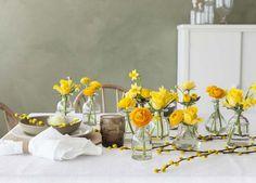 Pynt påskebordet med gule blomster som f.eks påskeliljer og ranunkler.