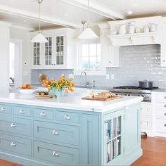 Soft blue kitchen island. Subway tile. White cabinetry.