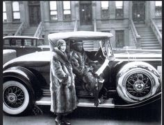 The Great Gatsby, 1932 An African American couple strike a pose wearing matching racoon fur coats. West 127th Street, Harlem NYC, 1932. James Van Der Zee, photographer.