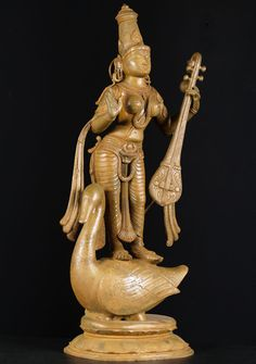 Goddess Saraswathi standing upon her vehicle, a beautiful swan, holding a veena with her right hand held open in the abhaya mudra.