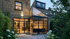Blee Halligan Architects has renovated and extended a house in north London, using black gridded glazing and pale brickwork to frame views of the garden