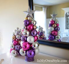 knitting needle tree---ornaments held together at the center by a knitting needle