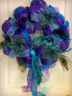 deco mesh peacock door wreath with beaded flowers, glitter, and feathers. $69.99, via Etsy.