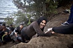 A refugee is helped as she climbs a hill towards the main road after arriving on a dinghy from the Turkish coast to the northeastern Greek island of Lesbos, Friday, Oct. 2 , 2015. The International Organization for Migration says a record number of people have crossed the Mediterranean into Europe this year.