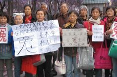Chinese petitioners protest in front of the Jingxi Hotel in Beijing, holding banners saying