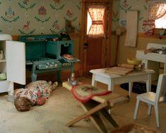 Corinne May Botz a trouvé et photographié des maisons de poupées miniatures reproduisant des scènes de crimes et suicides créées par la criminologue Frances Glessner Lee dans les années 40 et 50 pour entraîner des inspecteurs de police à repérer des indices.(la boite verte)