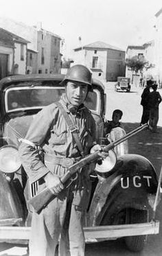 THE SPANISH CIVIL WAR, 1936-1939 Republican Forces: An armed Republican soldier preparing to depart for the Aragon Front in 1936. The car behind him bears the initials of the UGT (Unión General de Trabajadores - General Union of Workers).