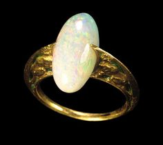 Gold and enamel opal ring, the shoulders decorated with green enamel expanding to grip the opal bezel, secured by claws at the front and back. Paris c. 1900 , René Lalique (1860-1943).
