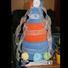 """Towel Cake I made for sister in laws bridal shower.  Used wash cloths to make """"roses"""" scale for the cake base and then rolled towels, safety pinned ends together and stacked using pins to secure all towels to each other as stacked. Decorated with ribbon."""