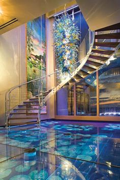 Glass floor with pond underneath and a Dale Chihuly up above.