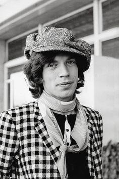 Mick Jagger in a newsboy cap, scarf, and checkered jacket is everything