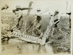 Members of the Canadian Forestry Corps carry split logs across the Souchez River in France.