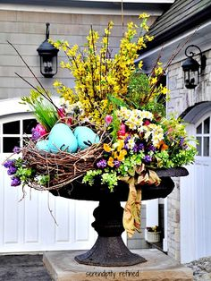 Spring urn planter flower arrangement with forsythia tulips daffodils and bird nest. Serendipity Refined