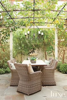 Wood created a secret-garden feel for an outdoor dining area with plenty of greenery and a wall-mounted clamshell fountain. The chairs are b...
