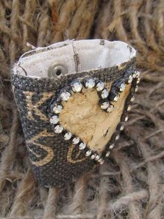 Idea for burlap ribbon bracelet - line with fabric, use snaps, and decorative broach or other bauble.....