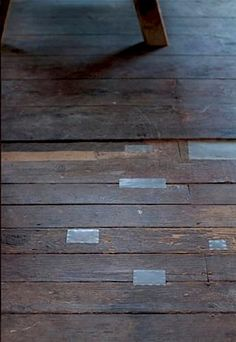 Wood floor patched with tin. Would be perfect, cheap, and easy for the house.