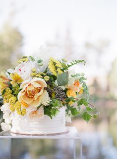 Simple white cake overflowing with yellow flowers
