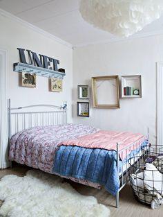 Makuuhuoneen sänky on Iskusta ja rautakorit kirpputoreilta. Kattovalaisimen ja suurimman täkin Katja on tehnyt. Yöpöytinä toimivat taulukehyksistä tehdyt seinälaatikot.