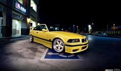 Night picture of a dakar yellow BMW e36 coupe on cult classic OZ AC Schnitzer type 1 wheels