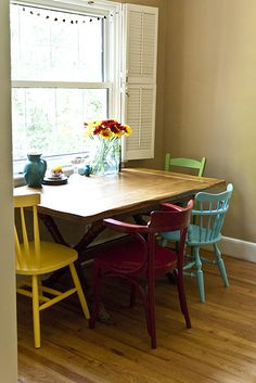 I want mismatched chairs around a wooden table like this.. very cute kitchen table idea. Maybe add a bench along the wall side