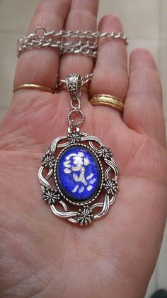 Colorful and cheerful necklace made with gentle white flower drawing on a blue glass, bordered in an antique round pendant . Part of my nature