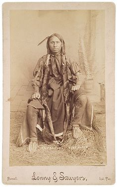 A seated young Comanche man poses for the camera wearing a polka-dot cotton shirt, his hair wrapped in long otter pelts, and wears hide leggings with flowing twisted fringe. Native American Music, Native American Pictures, Native American Beauty, Indian Pictures, Native American History, American Indians, Sioux, Comanche Indians, Cherokee