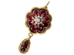 Antique Garnet Diamond Locket Back Pendant. During the Victorian era cabochon garnets were called carbuncles. Appearing as a single carved gem, 8 carbuncles have been shaped and fitted together to form a cluster dome with a scalloped perimeter. Star with 9 old mine cut diamonds; twisted rope border of 15K gold. Circa 1860