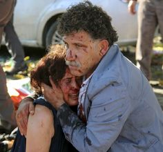 An injured man hugs an injured woman after an explosion during a peace march in Ankara, Turkey, killed 97