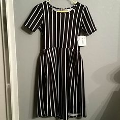 Lularoe Amelia Dress New with tags. Rare!! Black with White stripes popular Lularoe Amelia dress. Back has exposed silver zipper, hidden pockets in the skirt! Super comfortable,  size XS LuLaRoe Dresses