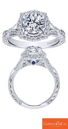 A detailed Gabriel & Co. Amavida 18k White Gold Diamond and Sapphire Halo Engagement Ring. The Sapphire stone underneath the center stone adds such a perfect color tone to this gorgeous piece! Discover your dream engagement ring with Gabriel & Co.!