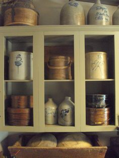 .Love the crocks,cupboard, buckets, and the dough box filled with wooden bowls beneath the cupboard.