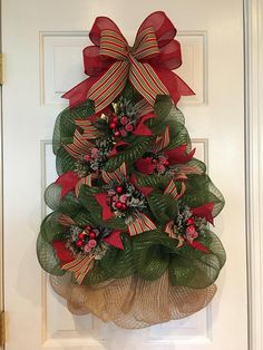 ITEM DESCRIPTION This glittering Christmas tree wreath has been carefully sculpted out of deco mesh, adorned with pomegranate, pear, or apple picks with pine cones and complementary ribbons. Tree can sit on floor resting against a wall or fireplace screen, so it can be used as a smaller