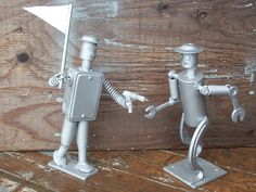 Tiny Metal Men! Robot Men Created by J.R. Hamm Made out of recycled scrap metal and painted silver. #lazer #gun #flag #running