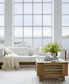 Beautiful floor to ceiling windows in this living room. Whites, greens and wood. Stunning view