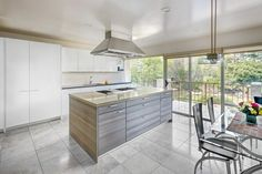 The clean lines and subtle colors of this modern kitchen let the outdoor views take center stage.