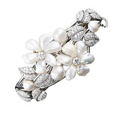 RUSER Freshwater Pearl Flowers and Diamond Leaves Bangle. Shimmering freshwater pearl flowers are entwined with glittering platinum and diamond leaves in this unique work of jewelery art. The underlying bangle bracelet is composed of 18 karat white gold wires.