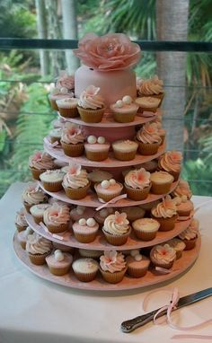 "Stunning wedding cupcake tower  I kind of like this idea. The tiny cake on top to ""cut"" for the bride and groom, and cupcakes for everyone else to eat. So cute, too. hmm.. cupcake"