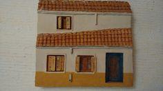 Fachada de casa con tejado a dos aguas de escayola, madera, cristal y cerámica. Año 1985 por  Javier Vega Regueiro.