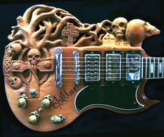 "Commissioned by David Ledogar of Massapequa, NY.  Started out as a white 1975 Gibson SG Standard - David wanted his SG to represent the Goth style. He wanted Skulls, tombstones, crosses and a big scary tree. We sent designs back & forth by email until we came up with the ""Chiller"". Dave sent along the cool skull pot knobs. Nice touch! The finish is a dark walnut oil stain."