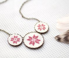 Cross stitch necklace with three dusty pink ethnic ornament in bronze