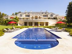 This excessive mansion has stucco walls, paneled roofing, large terrace with covered patio below, dual columns, a large pool, stone decking, and simple lounge furniture.
