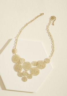 <p>Shine brighter than a star by completing your ensemble with this golden statement necklace. Detailed with dazzling array of filigree disks, this delicate accessory is certain to earn your outfit a galaxy of charming smiles and enchanting compliments.</p>