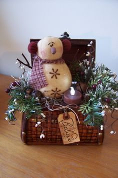 A vintage chest woven with brass stripes is the base for this sweet snowman...... Embellished with pine, pip berries, rusty jingle bell, a grungy hang tag and a cinnamon rolled, battery operated tea light.  $24