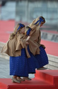 Catharina-Amalia, Princess of Orange (C) and Princesses Ariane and Alexia walk toward a boat on 30 April 2013 prior to take part in a water pageant on the river IJ in Amsterdam on the day of the new King's investiture