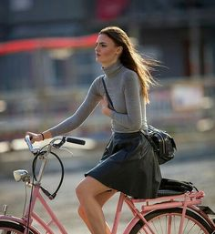 Tight gray turtleneck and flared black leather dress on bicycle