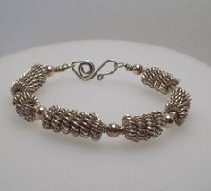 Sterling silver hand wound wire beads,spaced with 6 mm sterling silver beads, on a hand forged sterling cuff bracelet. Inner circumference 7 inches.     Hand forged swan clasp~    Weighs in at approximately 3/4 of an ounce.    Slightly oval,this will fit the average wrist~